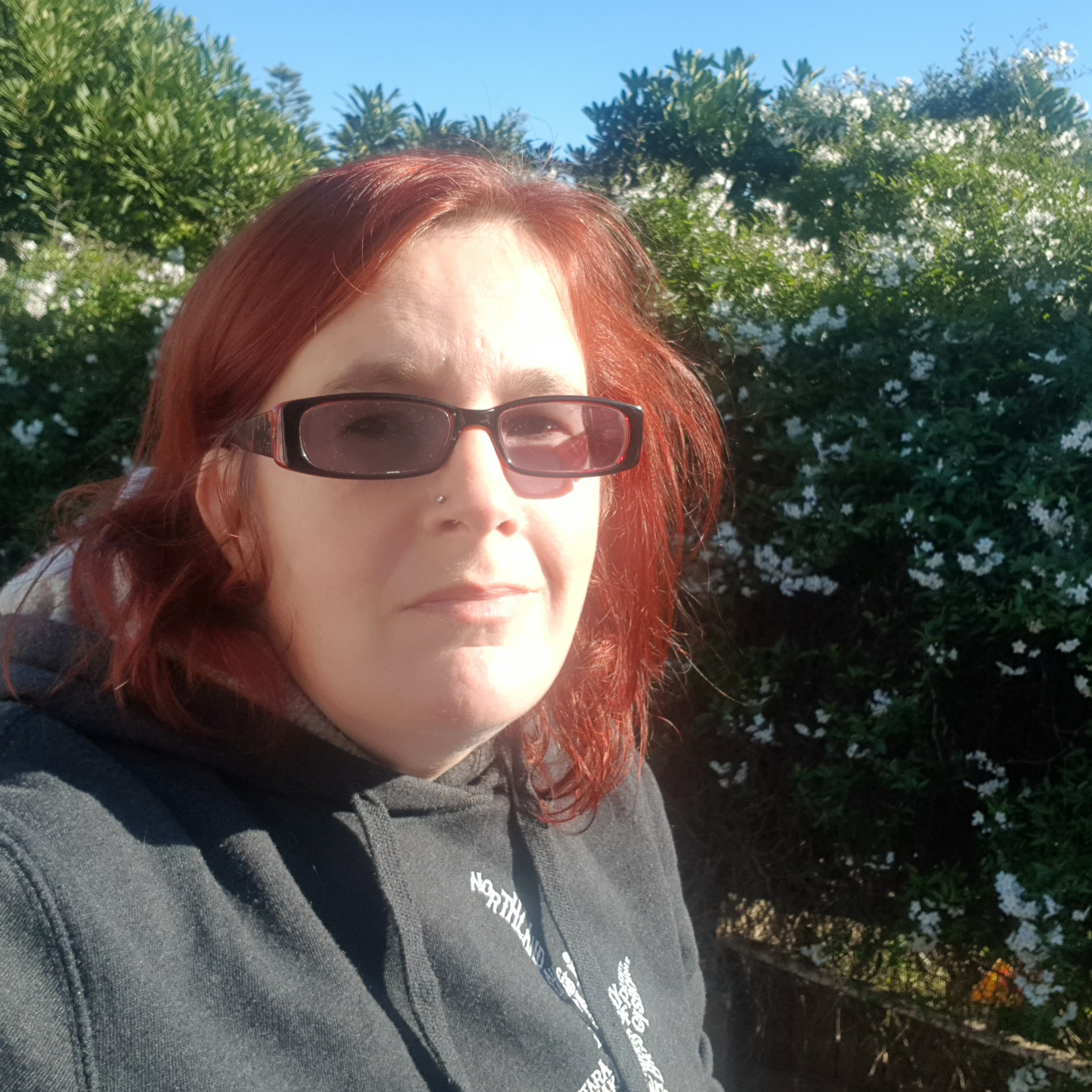 kitty fitton wearing glasses looking hopeful against a backdrop of clear blue sky and flowering jasmine.