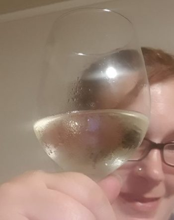 kitty fitton holding a glass of white wine up to the camera.