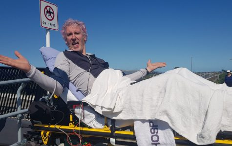 man on a gurney type stretcher with arms outstretched laughing against a blue sky.